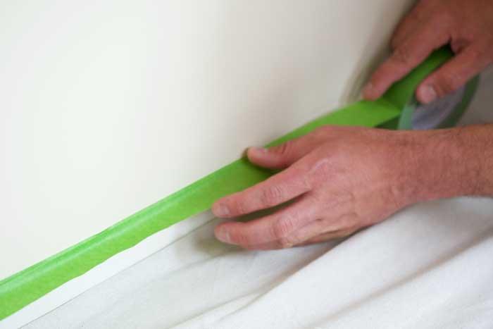 Aficionado aplicando cinta de pintor de la marca FrogTape® a un zócalo