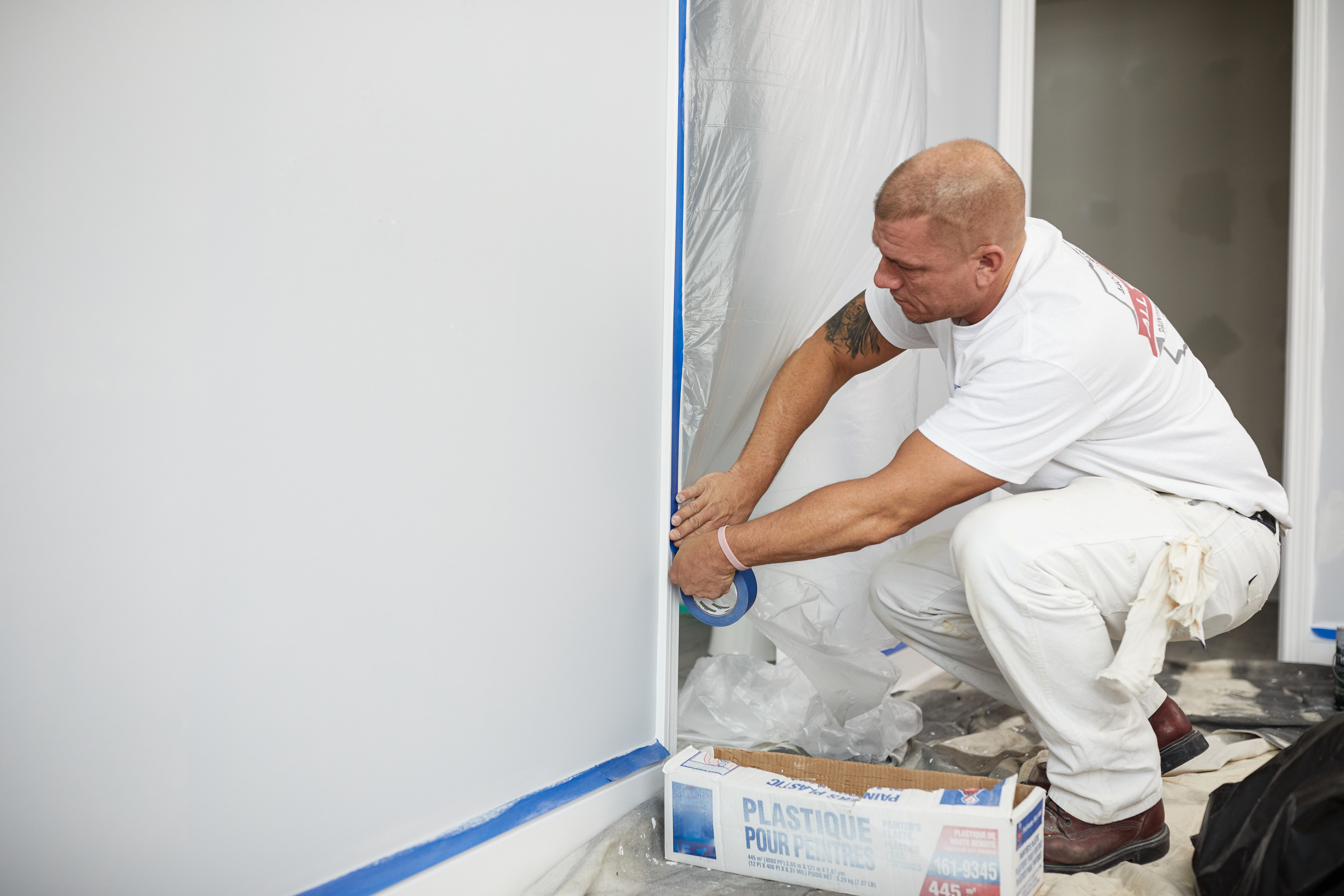 man applying frog blue painter's tape to white wall