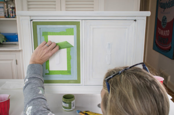 Woman peeling painter's tape off of a painted end table