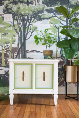 White painted end table with green and blue trim, sitting in front of plant wallpaper